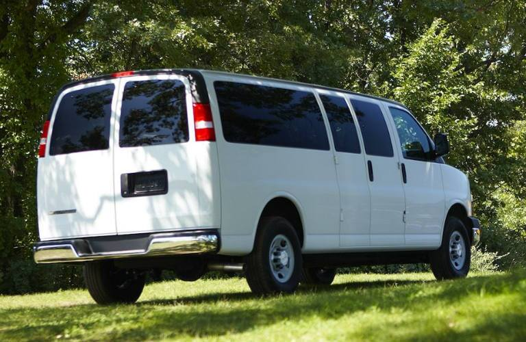 rear view of white 2018 chevrolet express cargo van on grass surrounded by trees