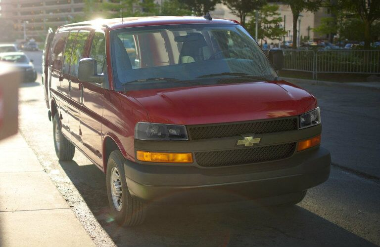 front view of red 2018 chevrolet express cargo van parked on curb of city sidewalk