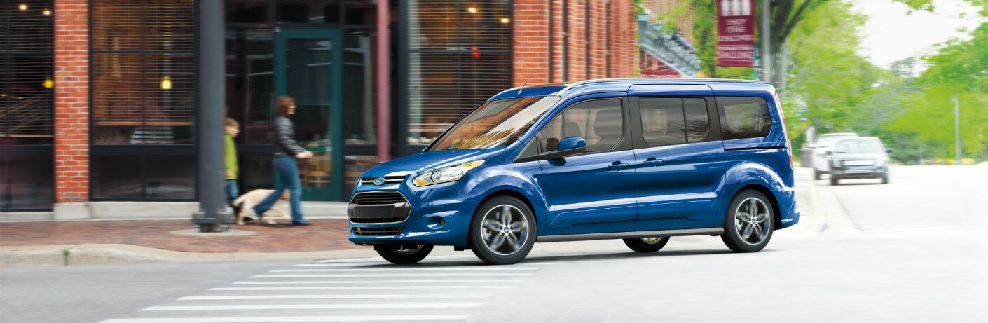 blue 2018 ford transit connect van driving through intersection of city