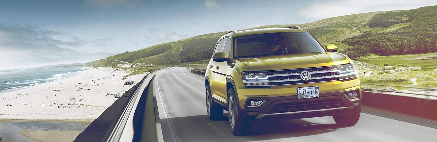 front view of yellow 2018 volkswagen atlas driving on road next to beach