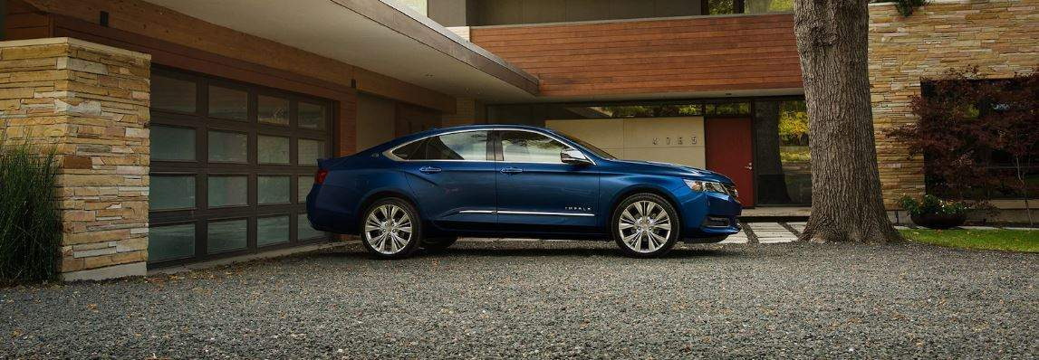 2018 chevy impala in blue parked outside a modern house garage