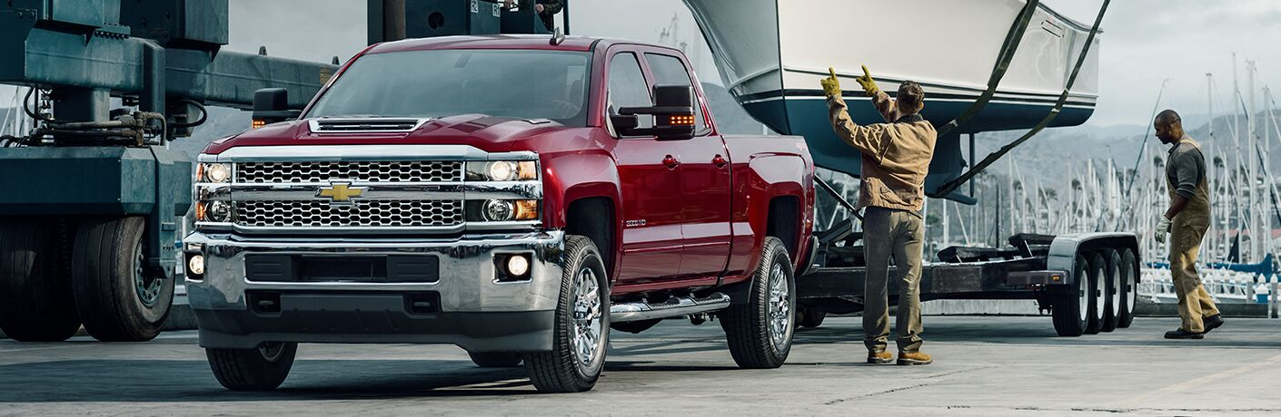 front and side view of red 2019 chevy silverado towing large boat trailer