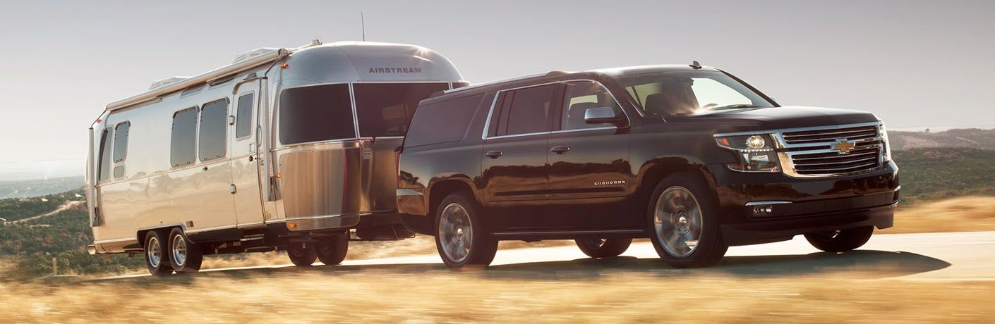 front and side view of black 2019 chevy suburban towing trailer