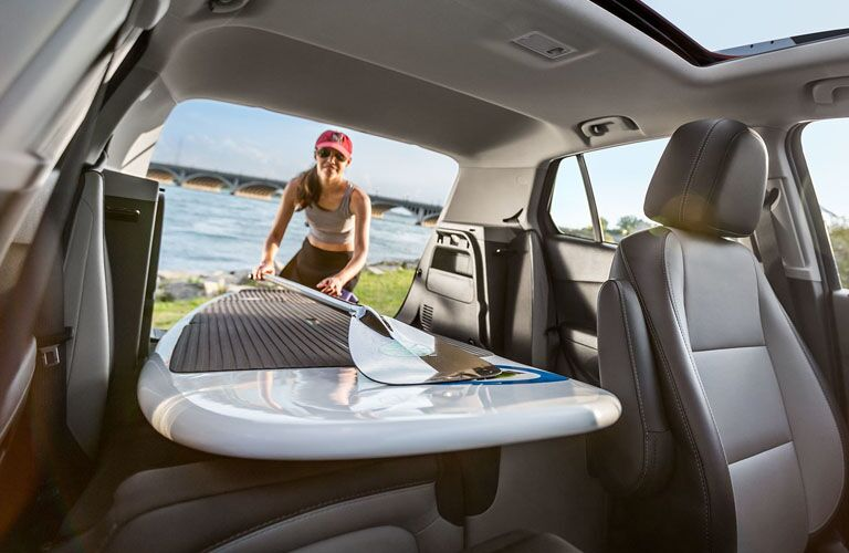 woman loading paddle board into cargo space of 2019 chevy trax