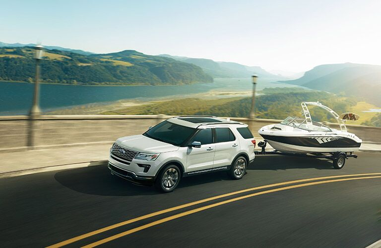 front and side view of white 2019 ford explorer towing boat