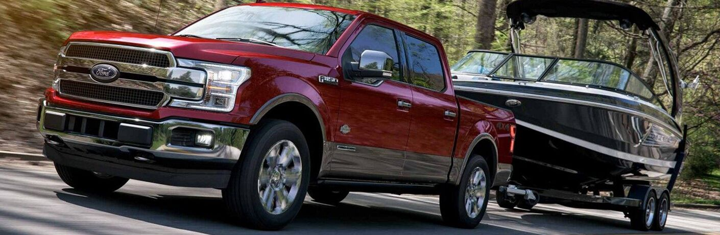 front and side view of red 2019 ford f-150 towing boat