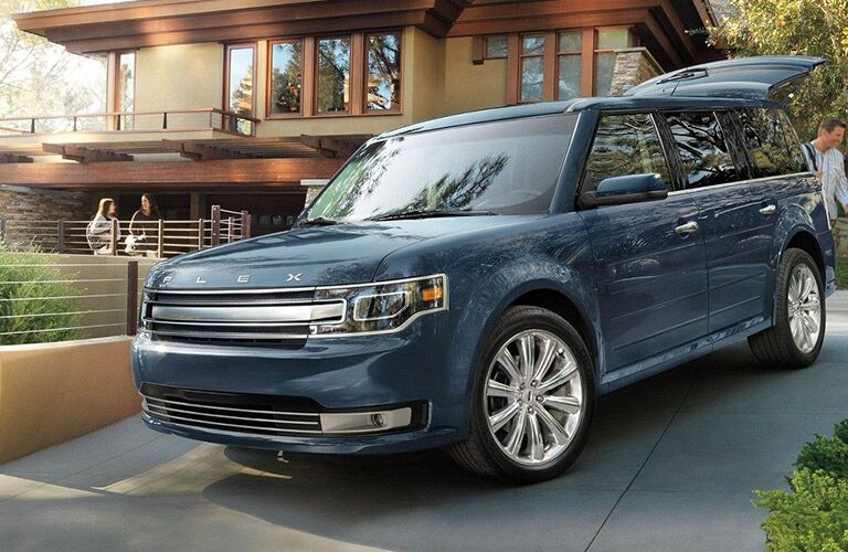 blue 2019 ford flex in driveway of home with liftgate open and people unloading luggage