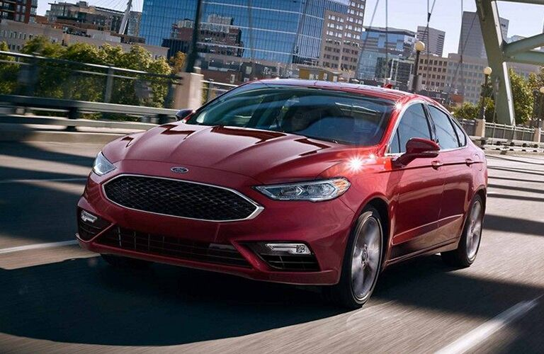 2019 Ford Fusion in red driving through a city