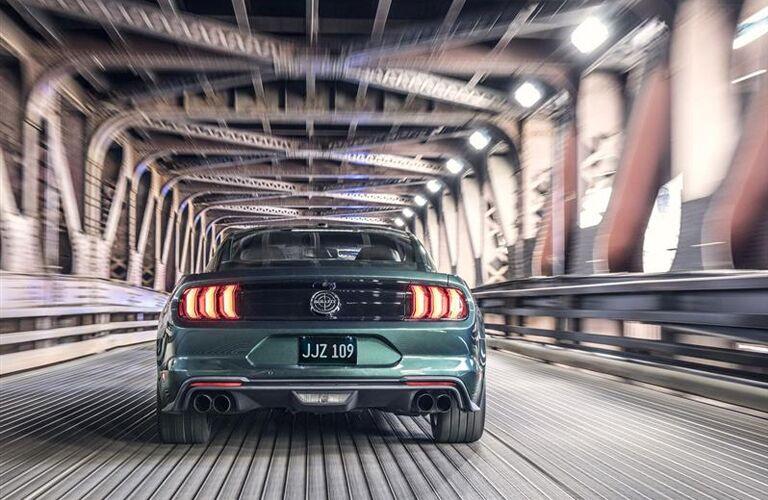 rear view of green 2019 ford mustang bullitt driving over bridge