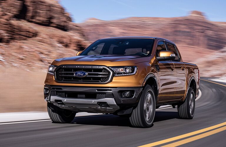 Front Driver Side View of an Orange 2019 Ford Ranger Driving on a Road with Desert Rocks in Background