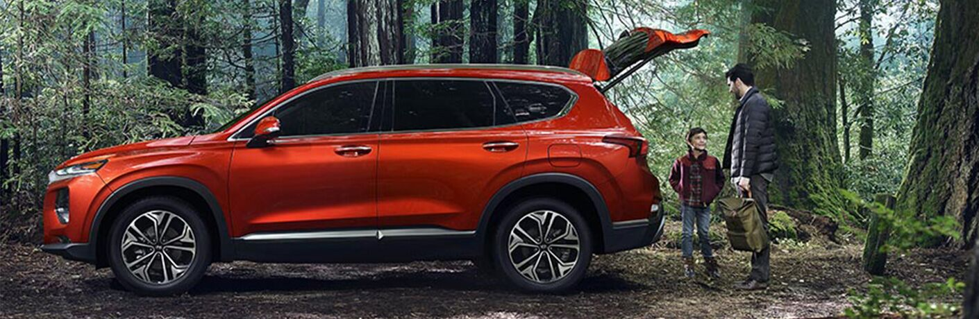 side view of orange 2019 hyundai santa fe in forest with liftgate open and father and son behind it with backpacks