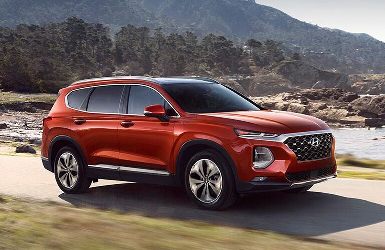 front and side view of orange 2019 hyundai santa fe driving on trail with river and trees behind it