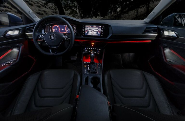front interior of 2019 volkswagen jetta with red ambient lighting including steering wheel and infotainment interface
