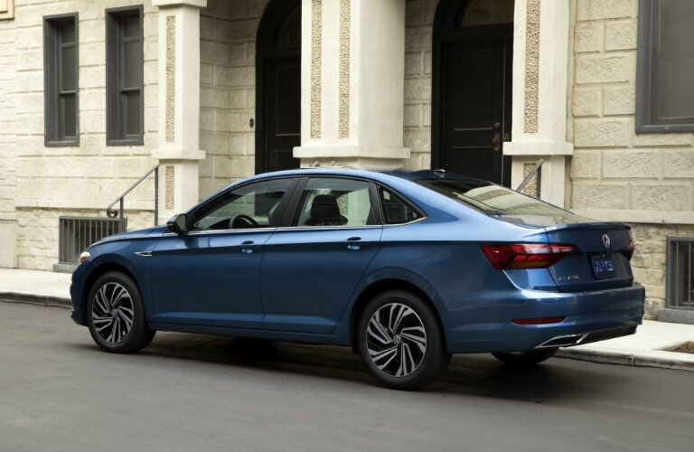 rear and side view of blue 2019 volkswagen jetta parked on street in front of stone building