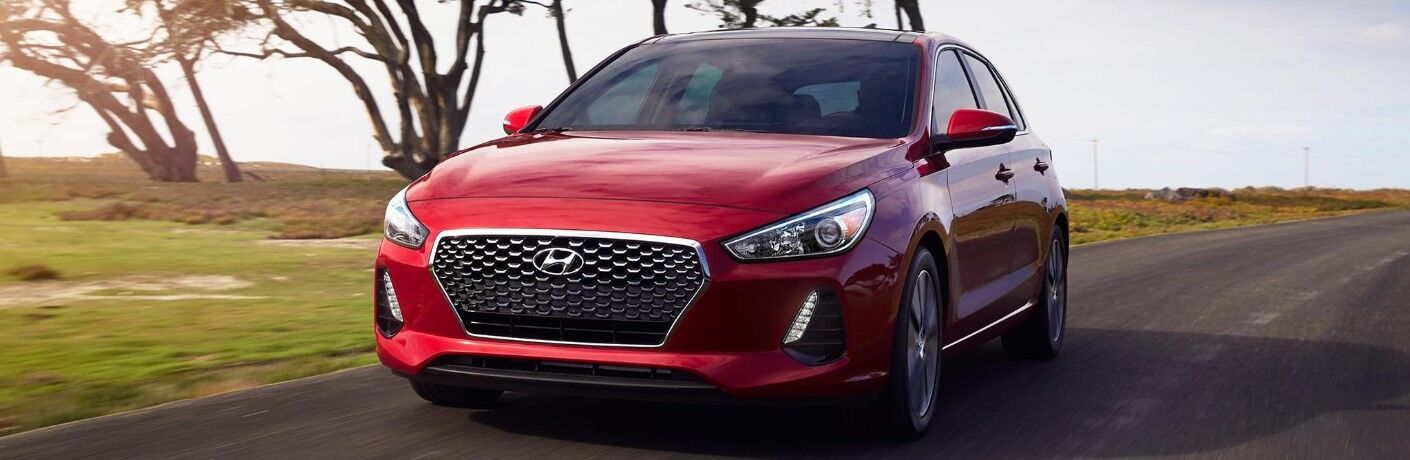 Front Driver View of a Red 2019 Hyundai Elantra GT Driving Down a Road with Trees in the Background