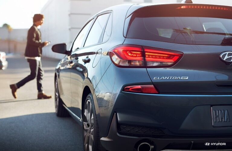 Rear Driver Side View of a Blue 2019 Hyundai Elantra GT with a Person Walking in the Background