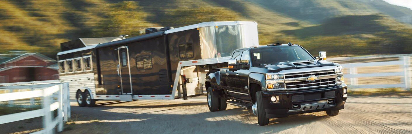 Black 2019 Chevy Silverado HD pulling a large trailer on a blurry background