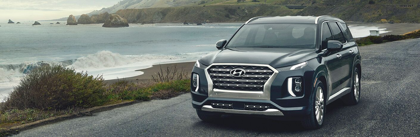 Front View of a Black 2020 Hyundai Palisade driving down a road with the Ocean in the Background
