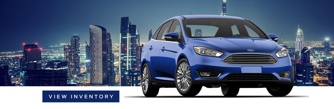 """blue 2018 ford focus in front of background of city skyline next to box with """"view inventory"""" text"""