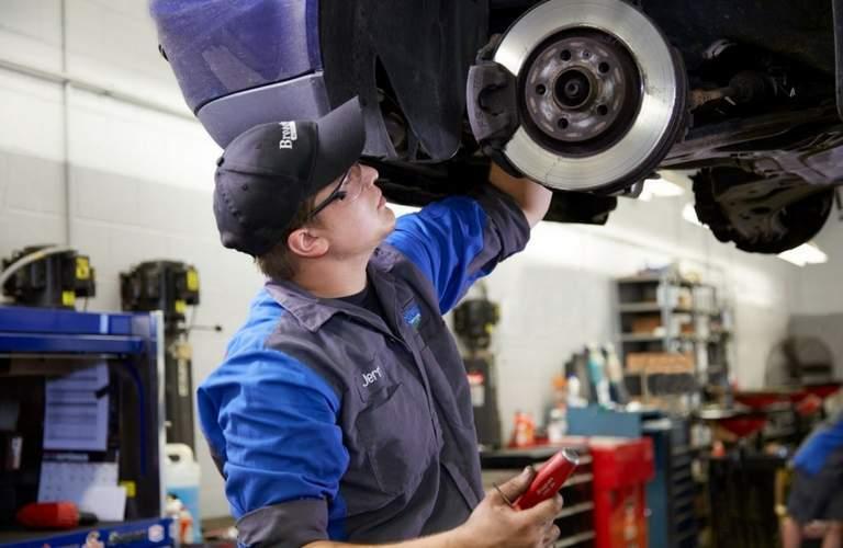 Broadway Automotive employee working on car brakes