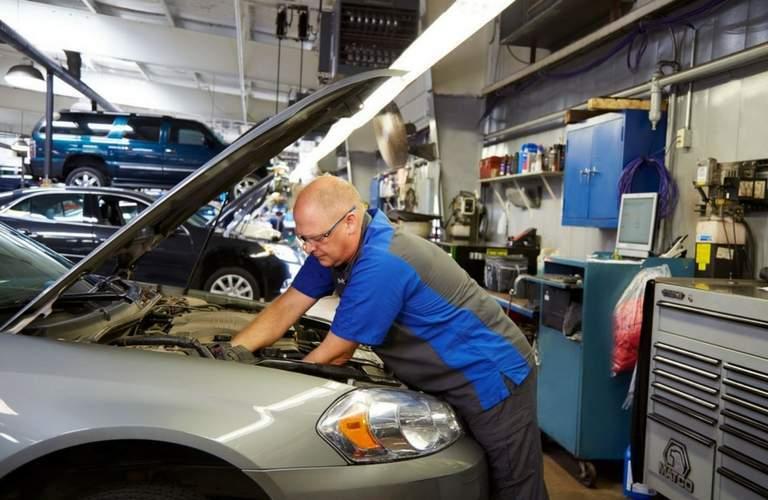 Broadway Automotive service technician employee working under the hood of a car