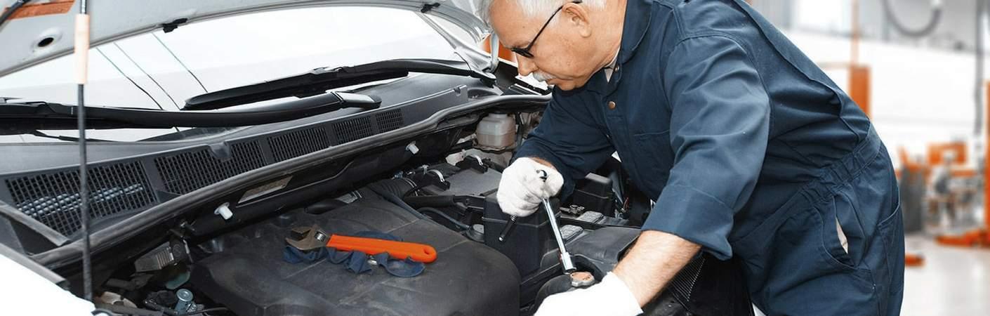 seasoned mechanic working under hood of car
