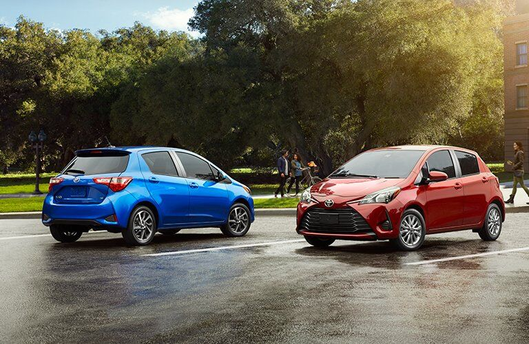 two attractive models of the 2018 Toyota Yaris parked in front of trees in a parking lot