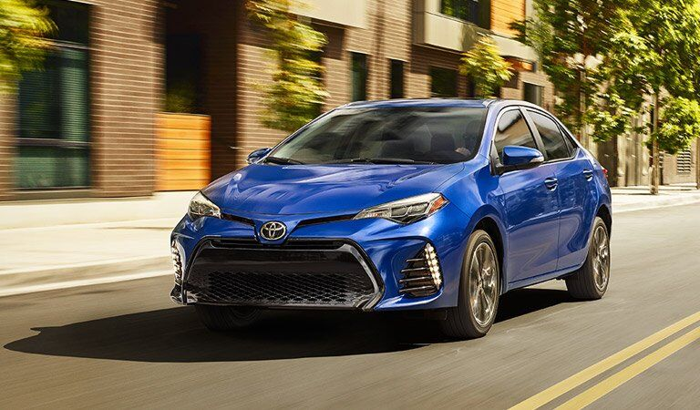 blue Toyota Corolla driving down the street