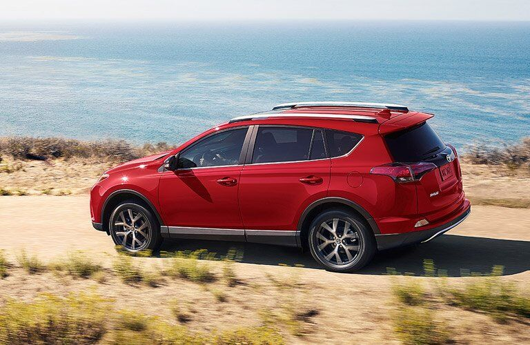 red 2017 Toyota RAV4 Hybrid driving by the water