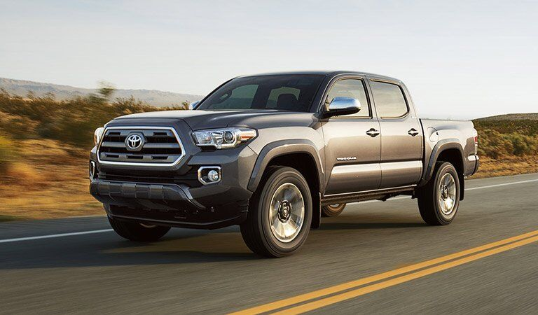 Toyota Tacoma driving on the road in the brushland