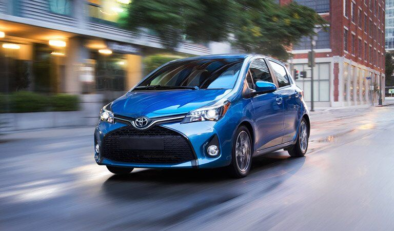 bright blue compact Toyota Yaris driving down the road