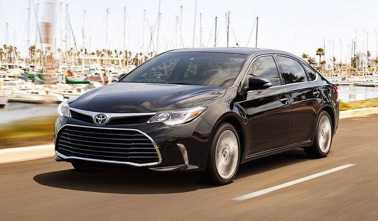 dark Toyota Avalon driving in front of a harbor