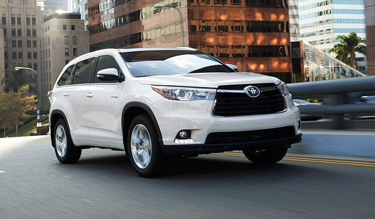 white Toyota Highlander driving in the city