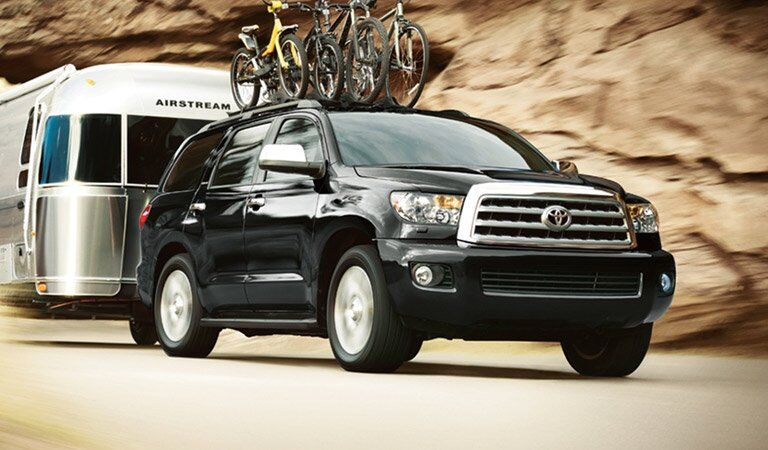 black Toyota Sequoia towing a motor home and hauling bikes