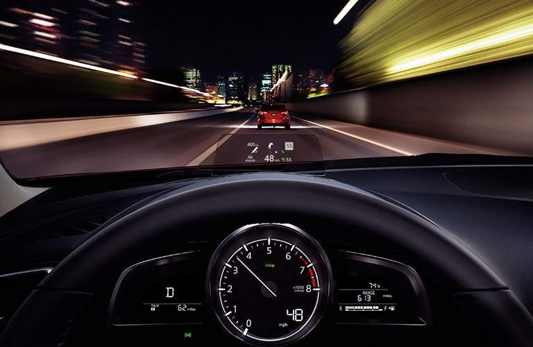 Gauge cluster and windshield view through the 2018 Mazda3 with a red Mazda3 driving ahead