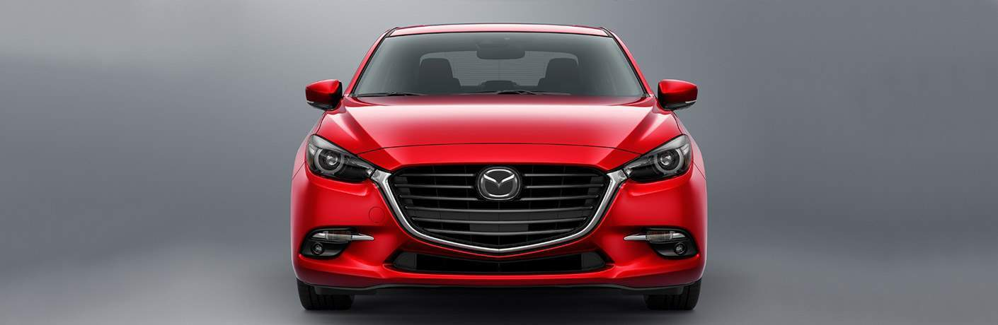 Front end of red 2018 Mazda3 4-door sedan on gray background