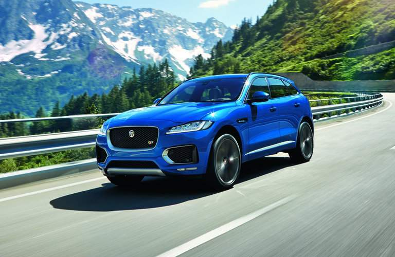 blue 2017 Jaguar F-PACE driving through mountains on a curvy road