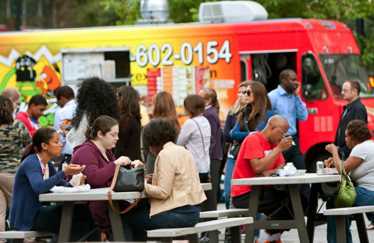 people eating on benches after getting food from a food truck