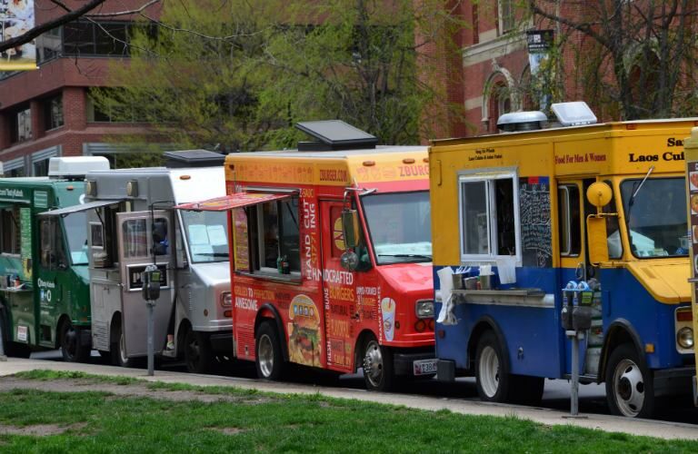 food trucks lined up on a street ready to feed eager crowds