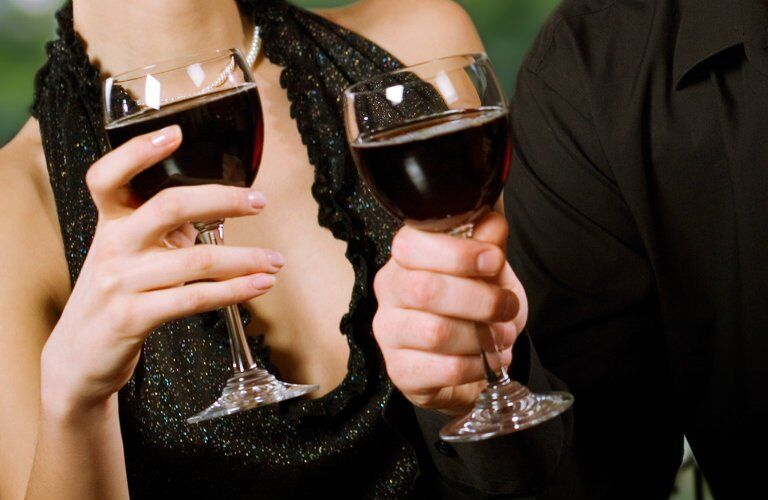 upper torso shot of a man and woman holding wine
