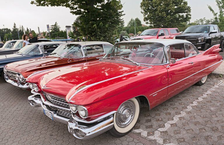 side view of a red classic car at a car show