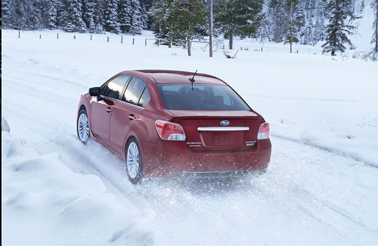 Red Subaru Impreza driving on a snow-covered road