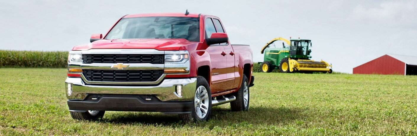 Red 2017 Chevy Silverado on a farm with a John Deere in the background