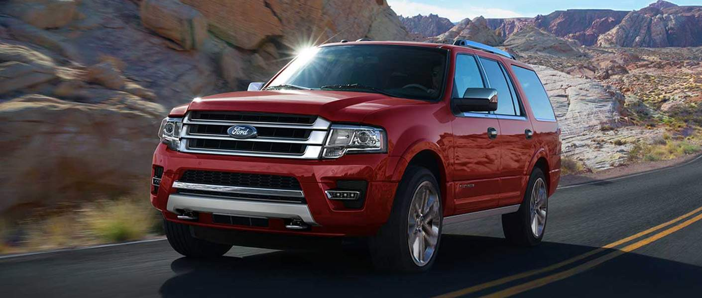 Ford Expedition Driving Near a Rock Wall