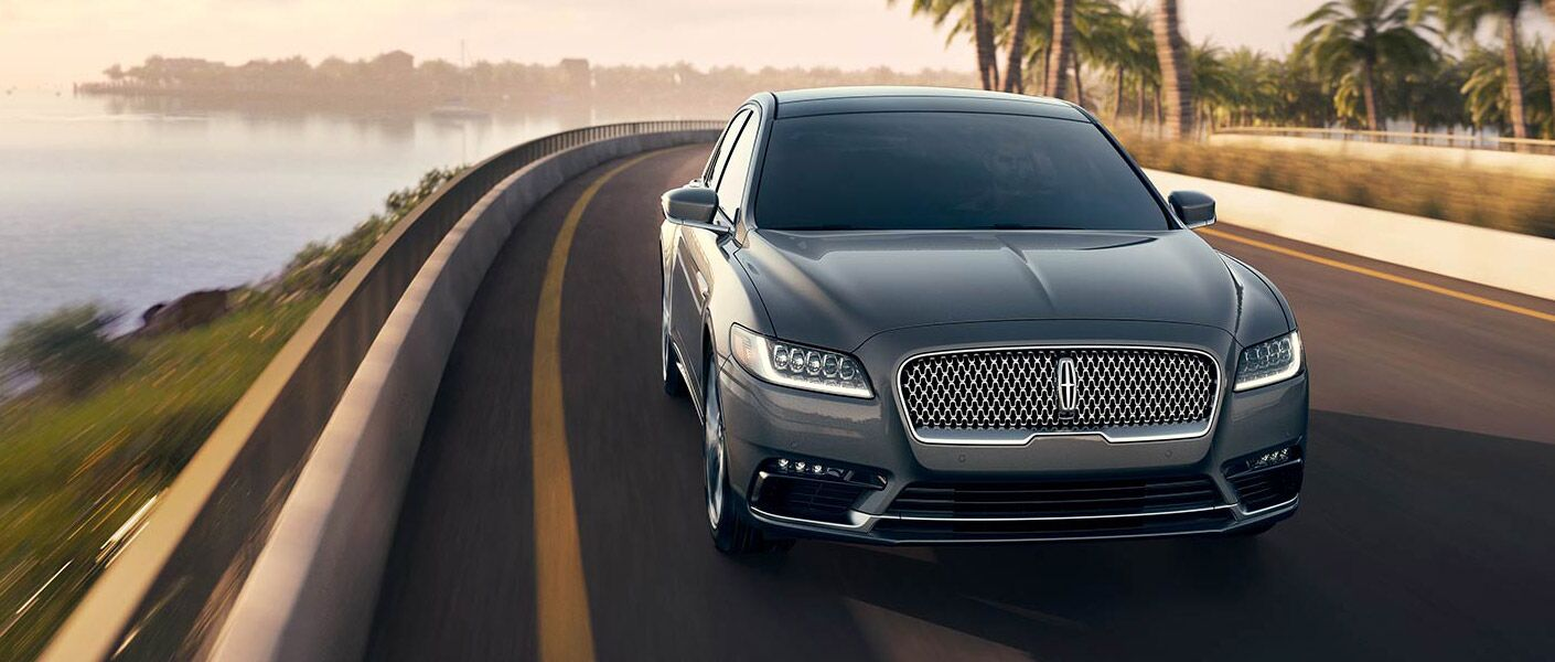 Gray Lincoln Continental driving on lakeside road