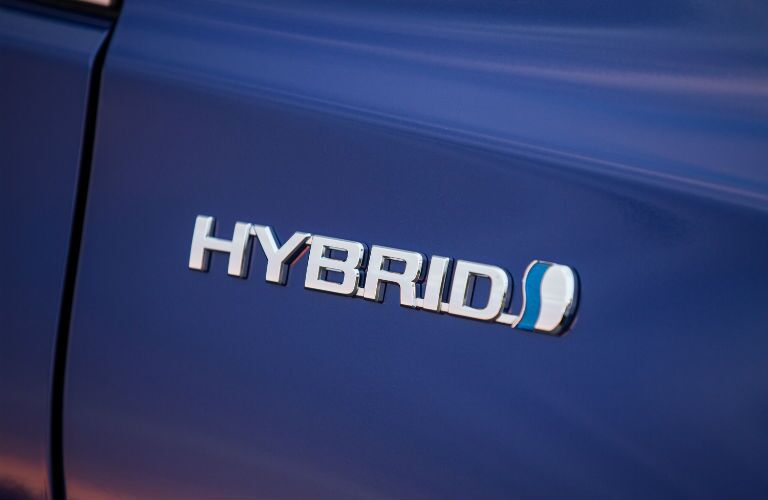 A photo of the hybrid badge worn by the Toyota Camry Hybrid.