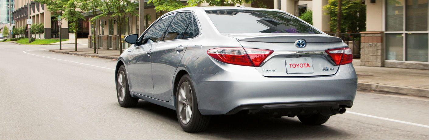 A rear left quarter photo of a used Toyota Camry Hybrid on the road.