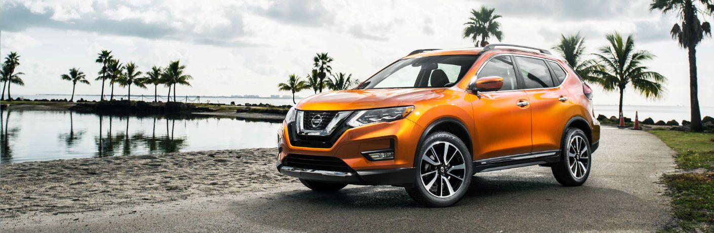 A left front quarter photo of the used Nissan Rogue parked on the side of the road.