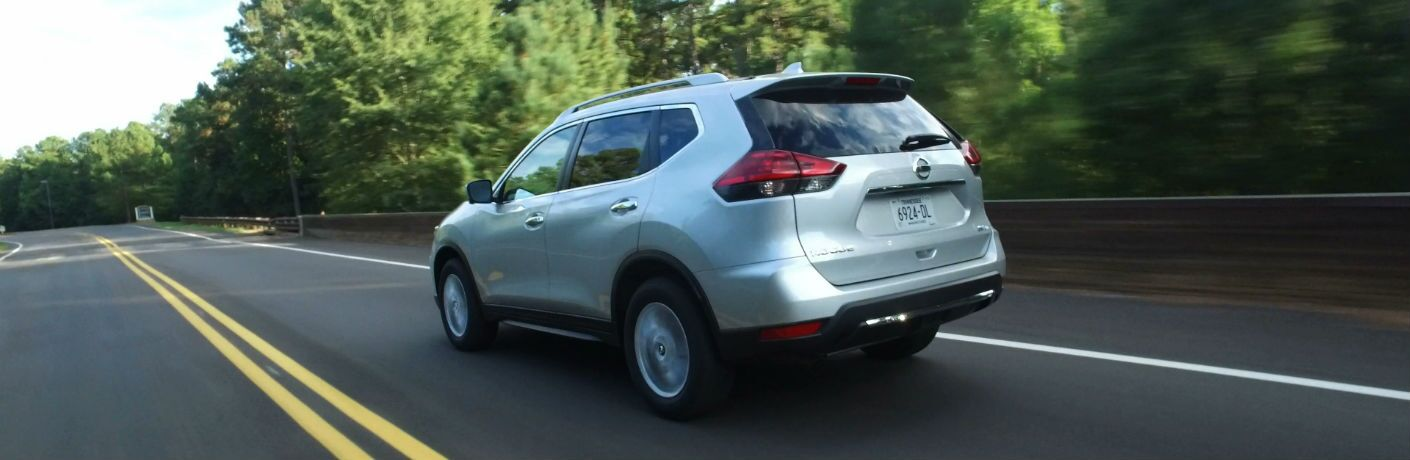 A rear left quarter photo of the used Nisson Rogue in motion on the road.