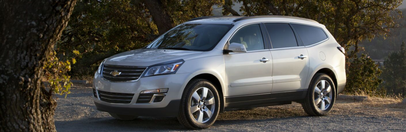 A left profile photo of the used Chevy Traverse parked in the woods.